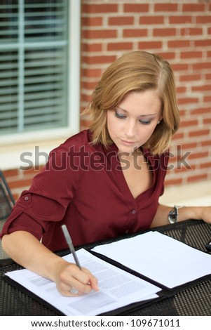 Attractive Professional Business Woman Writing and Reading Paperwork - stock photo
