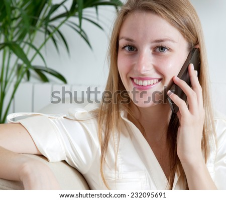 Attractive professional businesswoman sitting on a coach at home living room, making a phone call with a smartphone, joyfully smiling indoors. Working from home office. - stock photo