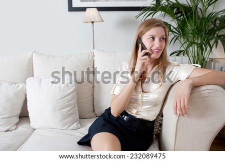 Attractive professional businesswoman sitting on a coach at home living room, working on a laptop computer and making a phone call with a smartphone, indoors. Working from home office. - stock photo