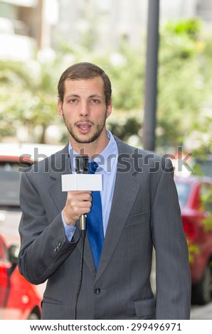 Attractive professional male news reporter wearing grey suit holding microphone, talking to camera from urban setting. - stock photo