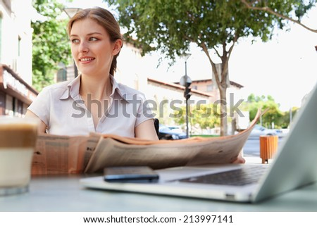 Attractive professional young business woman sitting at a coffee shop reading a financial newspaper and drinking a hot beverage, with a laptop computer and smartphone technology, outdoors.