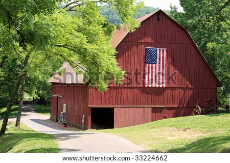 Attractive red barn with an American Flag - stock photo