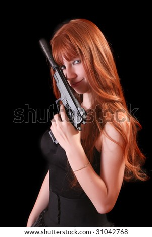 Attractive red girl with gun on black background - stock photo