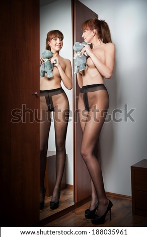 Attractive red hair model only in pantyhose looking into a mirror playing with a teddy bear. Fashion portrait of sensual long legs woman - indoor shoot. Sensual female posing near a wardrobe.