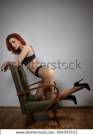 Attractive red hair model with black lingerie sitting provocatively on chair, gray background. Fashion portrait of sensual woman - studio shot. Beautiful redhead female in black posing provocatively. - stock photo