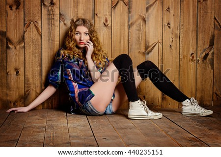 Attractive red-haired girl in checkered shirt and jeans shorts posing by a wooden wall. Youth style, fashion. - stock photo