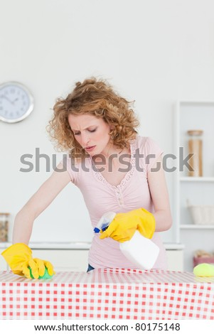 Attractive red-haired woman cleaning a cutting board in the kitchen in her apartment - stock photo