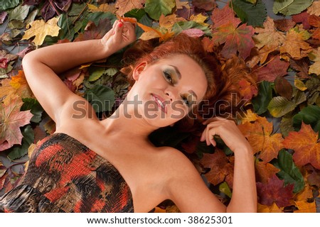 Attractive redhead in autumn leaves