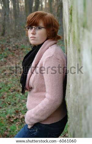Attractive redhead with glasses posing outside