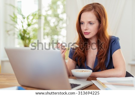 Attractive redhead woman eating breakfast and working or catching up on her social media on her laptop as she sits at the dining table at home