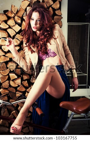 attractive redhead woman in high heels shoes lean on retro bicycle in apartment - stock photo