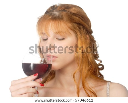 Attractive redheaded young woman drinking red wine.  Focus is on the girl, not the drink.