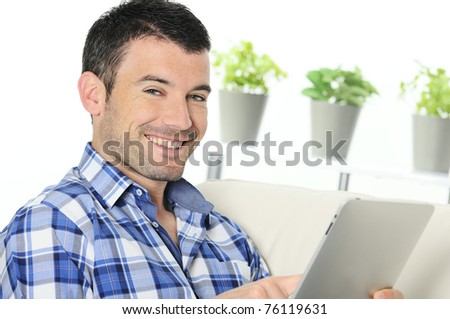 attractive relaxed and positive man is surfing on his tablet - stock photo