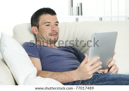 attractive relaxed and positive man is surfing on his tablet