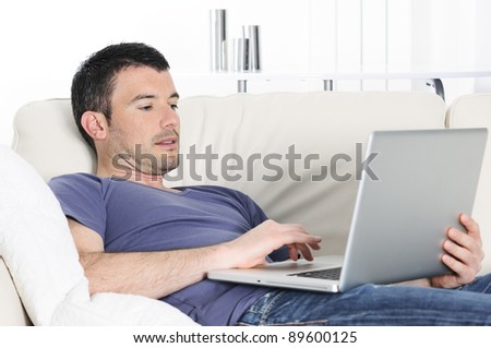 attractive relaxed man is working at home on a sofa