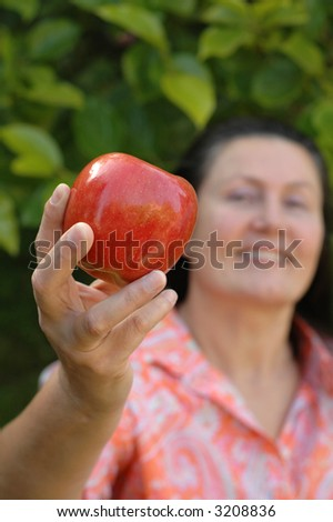 Attractive retired woman showing off a prize apple from her garden.  Healthy senior lifestyle concept. - stock photo