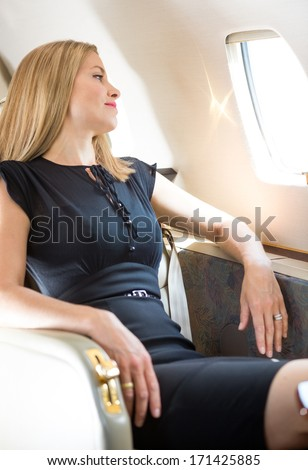 Attractive rich woman looking through window in private jet - stock photo