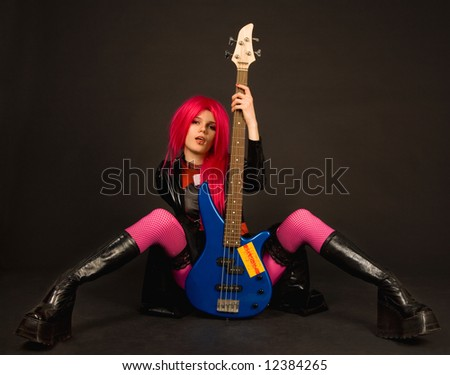 Attractive rock girl in crazy outfit sitting with bass guitar - stock photo