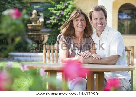 Attractive, romantic and happy middle aged man and woman couple in their forties, sitting together outside in a garden with flowers - stock photo
