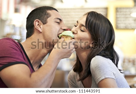 Attractive romantic couple sharing a cupcake in a coffee shop