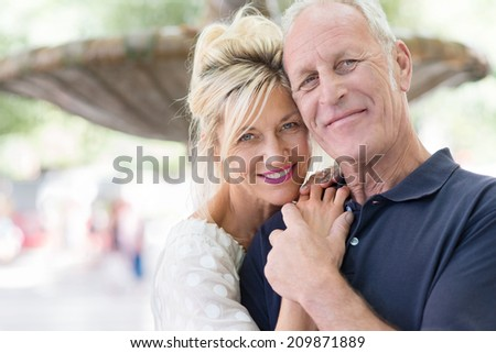 Attractive romantic middle-aged couple posing for their portrait with the heads close together and clasped hands in front of a fountain - stock photo