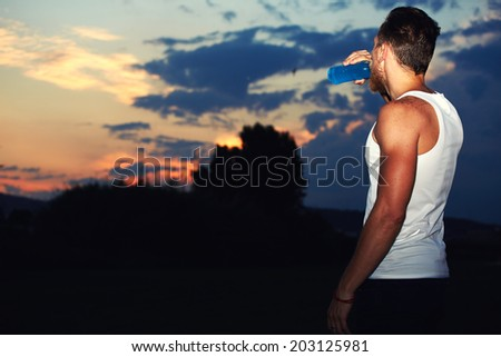 Attractive runner with muscular body enjoying amazing sunset drinking water, runner resting after intensive evening jog, health lifestyle and fitness concept - stock photo