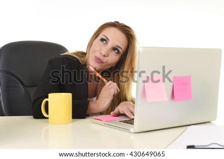 attractive 40s blond businesswoman working at office laptop computer sitting on the desk absent minded and thoughtful smiling happy as if thinking of vacation isolated on white background - stock photo