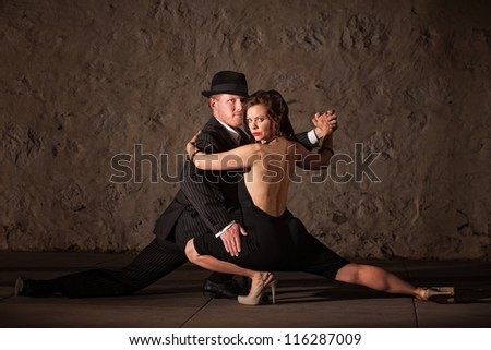 Attractive 1920s tango dancers holding each other near the floor - stock photo