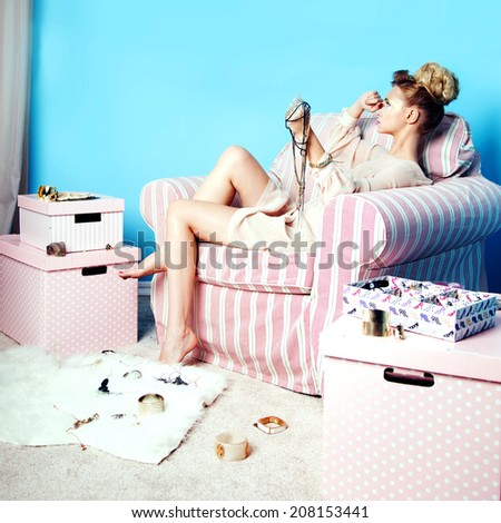 Attractive sad blonde beauty sitting in room with a lot of jewelry, thinking. - stock photo