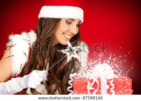 attractive santa woman with magic wand and magic Christmas present - stock photo