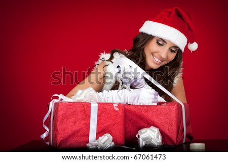 attractive santa woman wrapping Christmas presents with ribbon - stock photo