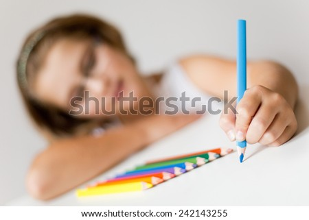 attractive school girl painting, focus on her painting hand  - stock photo