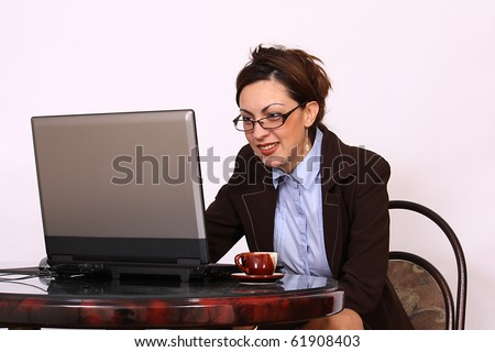 Attractive secretary with eyeglasses working on lap top computer - stock photo