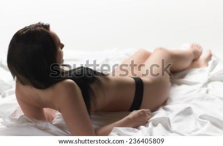 Attractive seminude woman wearing white fabric and she lying on the white bed sheets