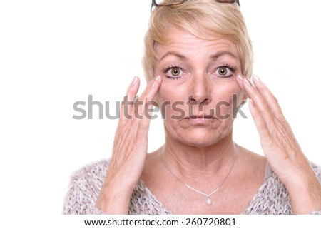 Attractive senior blond woman with a wide-eyed expression and her glasses on her head checking her complexion as she looks into the mirror - stock photo