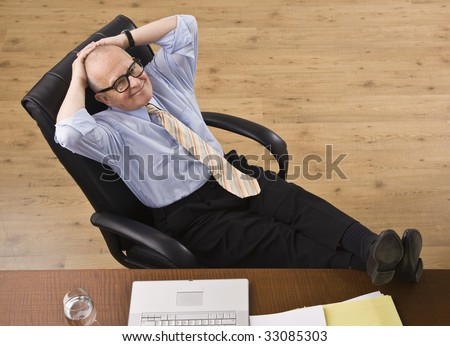 Attractive senior business man relaxing with feet on desk, reclining in chair, smiling at camera. Horizontal - stock photo