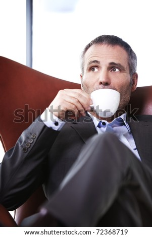 Attractive senior businessman in grey suit sitting in red office chair looking outside and sipping coffee. - stock photo