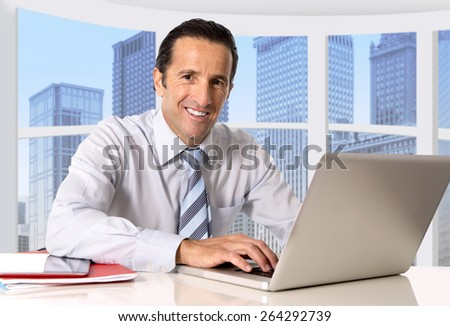 attractive senior businessman working in business district office at computer laptop desk smiling relaxed in successful career and work promotion and success concept - stock photo