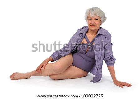 Attractive Senior Citizen Lady wearing a swimming suit on a white background - stock photo