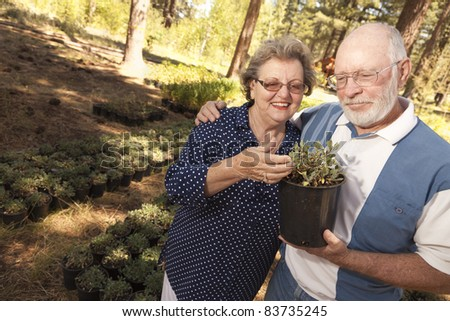 Attractive Senior Couple Overlooking Potted Plants at the Nursery. - stock photo