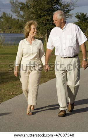 Attractive senior couple walking together in a park - stock photo