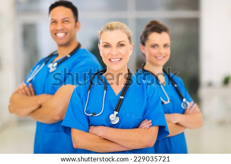 attractive senior female doctor leading medical team at hospital - stock photo