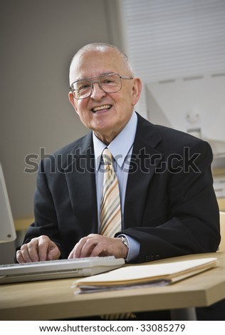 Attractive senior male smiling at camera, working on keyboard at desk. Vertical