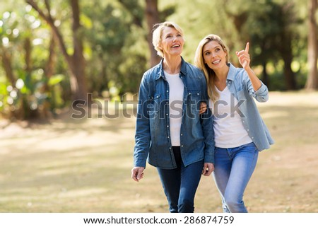 attractive senior mother with daughter relaxing outdoors - stock photo