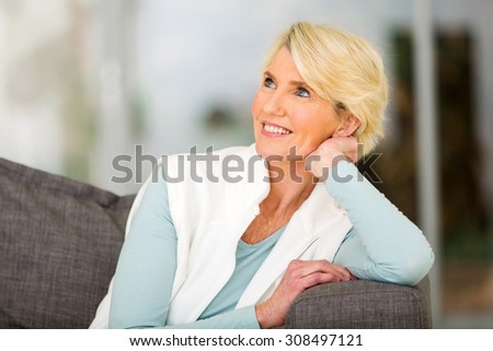 attractive senior woman daydreaming at home