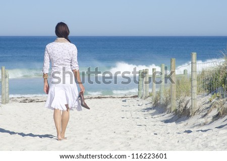 Attractive senior woman happy and joyful at beach, relaxed with high heel shoes in hand, isolated with ocean and blue sky as background and copy space. - stock photo