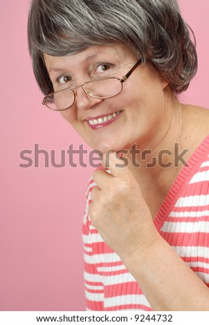 Attractive senior woman in glasses on pink background - stock photo