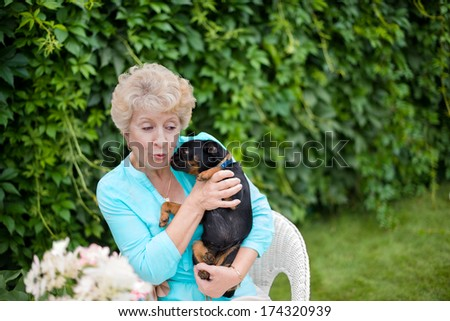 Attractive senior woman playing with her puppy in the backyard - stock photo