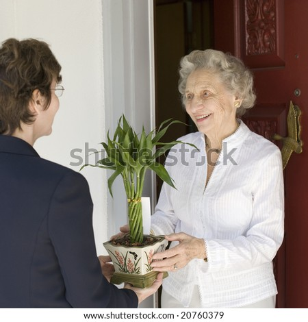 Attractive senior woman receiving gift of bamboo plant at front door - stock photo