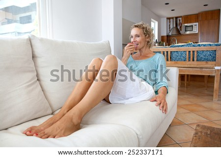 Attractive senior woman relaxing on a white sofa at home, biting into a healthy red apple. Mature woman enjoying eating fruit at home. Healthy eating and well being lifestyle, interior. - stock photo
